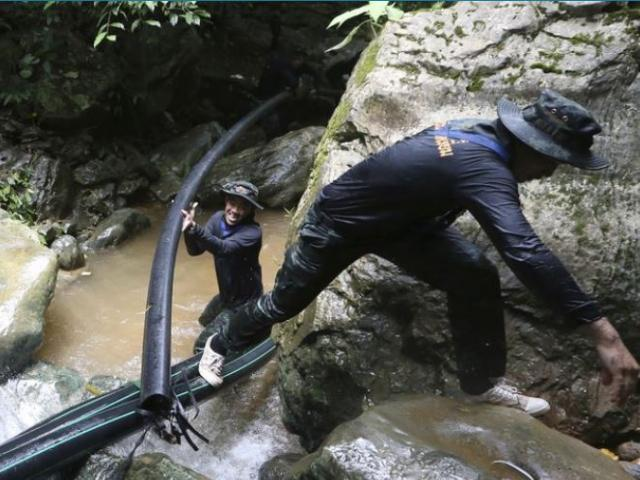 Thai soldiers drag a water pipe to bypass water from mountain not get back to inside a cave where 12 boys and their soccer coach have been trapped since June 23, in Mae Sai, Chiang Rai province, in northern Thailand.
