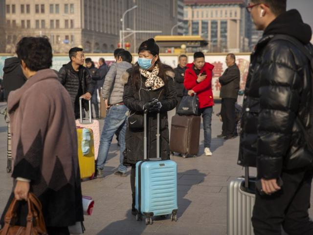 A traveler wears a facemask as she stands near the Beijing Railway Station in Beijing, Friday, Jan. 17, 2020. (AP Photo/Mark Schiefelbein)