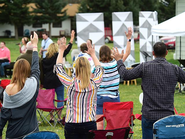 Church members raise their hands as Pastor Greg Payton leads a live outdoor service at The Rock Church in Laurel, Mont., Sunday, April 26, 2020. (Larry Mayer/The Billings Gazette via AP)
