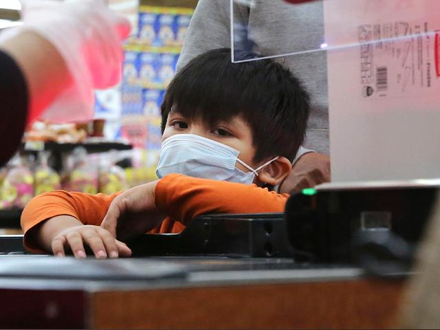 Amid social distancing during the Covid-19 outbreak, a young boy looks on during a transaction with the cashier at El Rancho grocery store in Dallas, March 26, 2020 (AP Photo/LM Otero)
