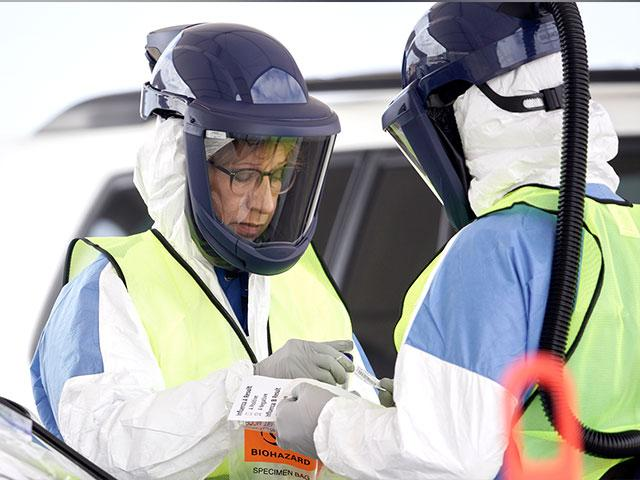 Nurses in protective gear handle a test for the coronavirus at a drive-thru testing location at Bryant Health's LifePointe campus in Lincoln, Neb., Tuesday, March 24, 2020. (AP Photo)