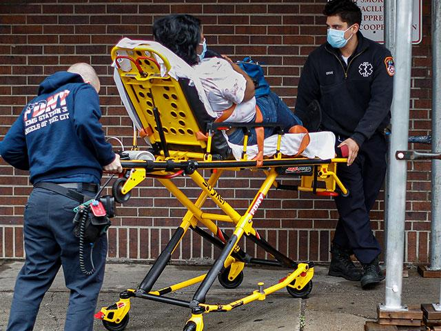 Emergency medical workers wear protective masks due to COVID-19 concerns while delivering a patient to the emergency room at Brooklyn Hospital Center, Sunday, March 29, 2020 (AP Photo/John Minchillo)