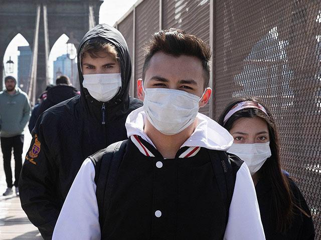 People wear masks as they cross the Brooklyn Bridge, Monday, March 16, 2020 in New York. (AP Photo/Mark Lennihan)