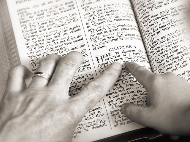 Dad and child pointing to Bible verse