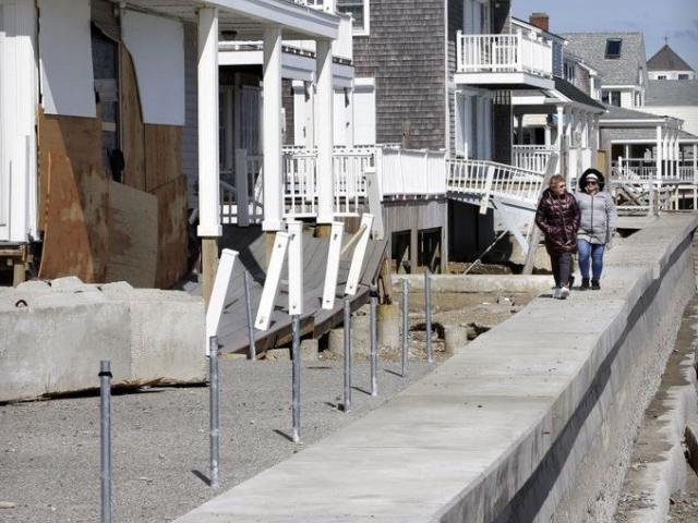 Two women walks along a seawall near damaged beachfront homes in Marshfield, Mass.