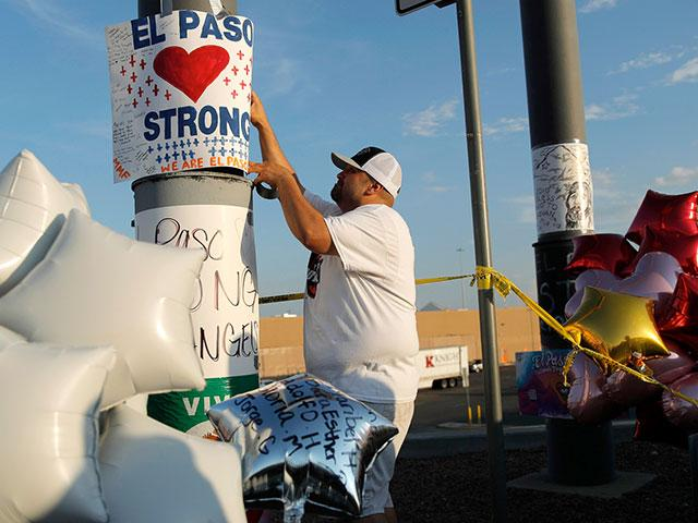 "In this Aug. 6, 2019 file photo, a man hangs up an ""El Paso Strong"" sign at a makeshift memorial at the scene of a mass shooting at a shopping complex in El Paso, Texas.  (AP Photo/John Locher, File)"