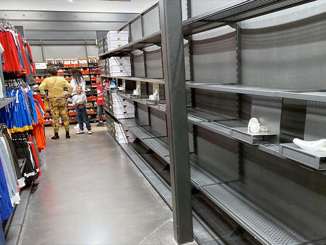 Shelves sit empty of shoes in a Nike outlet store, Oct. 5, 2021, in Castle Rock, Colo. (AP Photo/David Zalubowski)