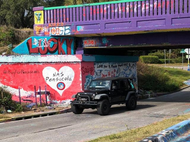 A vehicle drives by a tribute to victims of the Naval Air Station Pensacola that was freshly painted on what's known as Graffiti Bridge in downtown Pensacola, Fla., on Saturday, Dec. 7, 2019. (AP Photo)