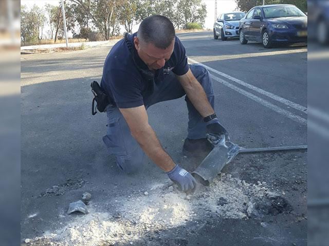 Police Officer Examines Spent Rocket, Photo, Israel Police Spokesman's Office