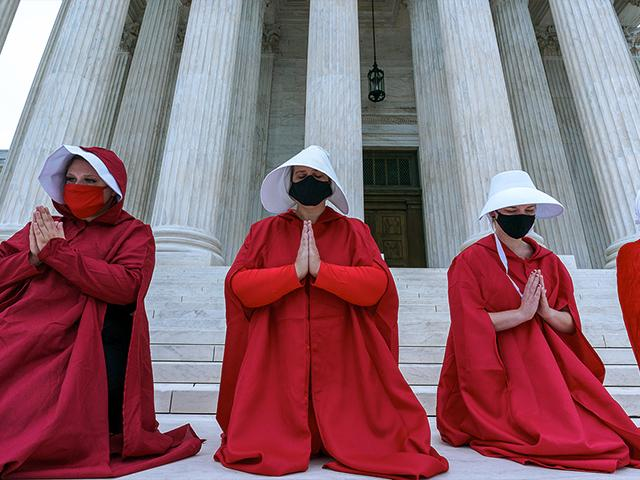 """Activists opposed to the confirmation of President Donald Trump's Supreme Court nominee, Judge Amy Coney Barrett, are dressed as characters from """"The Handmaid's Tale,"""" at the Supreme Court on Capitol Hill in Washington, Sunday, Oct. 11, 2020."""
