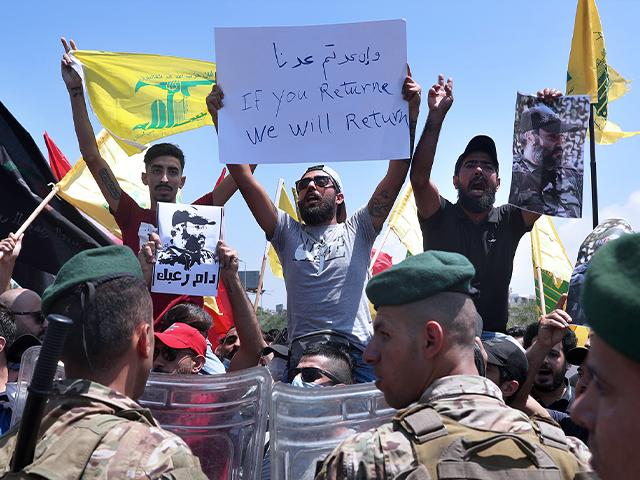 Lebanese army soldiers stand guard as Hezbollah supporters chant slogans and hold posters of the late Hezbollah military commander Imad Mughniyeh.Wednesday, July 8, 2020. (AP Photo/Bilal Hussein)