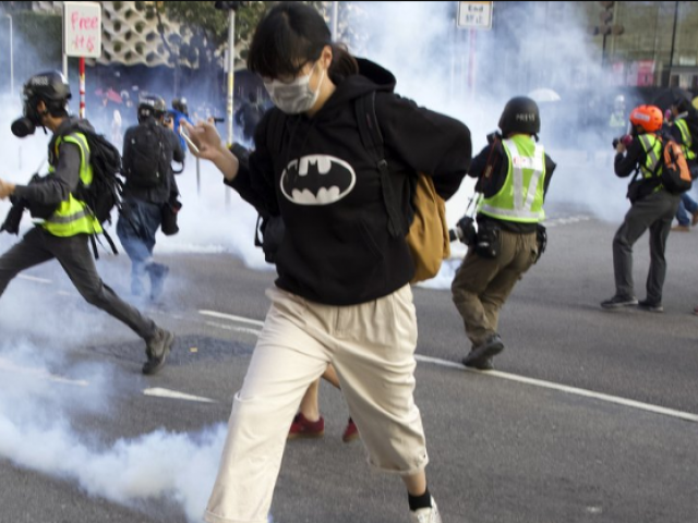 A pro-democracy protester runs away from the tear gas fired by riot police during a rally in Hong Kong, Sunday, Dec. 1, 2019. (AP Photo)