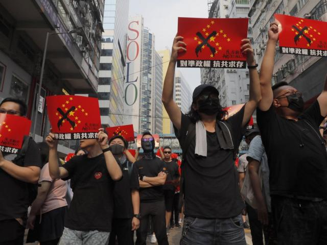 "Protesters march holding signs which reads ""Anti-Chinazi"" combining the elements of the Nazi swastika and Chinese flag in Hong Kong on Sunday, Sept. 29, 2019 (AP Photo/Kin Cheung)"