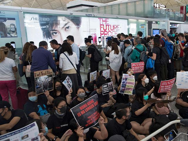 Travelers walk past as protesters hold a sit-in rally near the departure gate of the Hong Kong International Airport in Hong Kong (AP Photo/Vincent Thian)