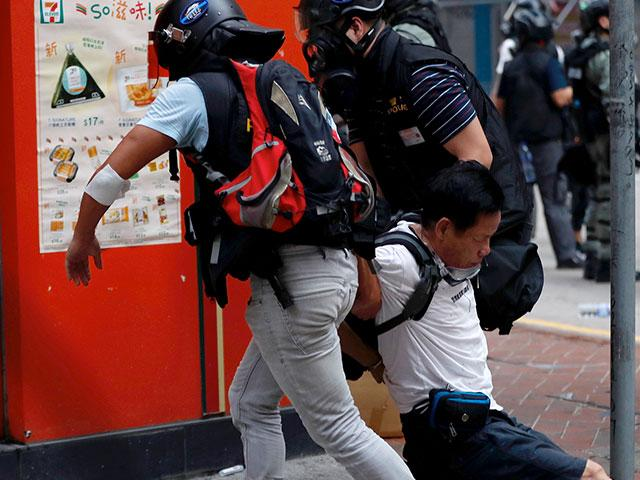 An injured anti-government protester is aided by others during a clash with police in Hong Kong, Oct. 1, 2019. Thousands of black-clad protesters marched as part of multiple pro-democracy rallies. (AP photo)