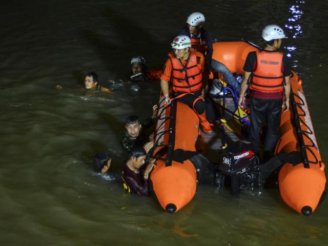 Rescuers search for victims of drowning in a river in Ciamis, West Java, Indonesia, Friday, Oct. 15, 2021. (AP Photo/Yopi Andrias)