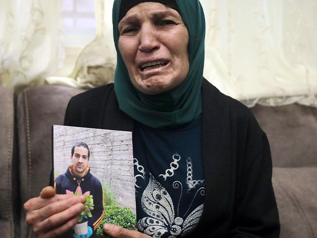 Rana, mother of Iyad Halak, 32, holds his photo at their home in eastern Jerusalem's Wadi Joz, Saturday, May 30, 2020
