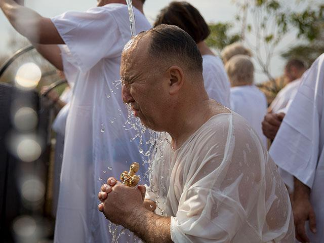 AP: A Cristian pilgrim takes part in baptism in the Jordan river during the Orthodox Feast of the Epiphany at Qasr el Yahud, the spot where John the Baptist is said to have baptized Jesus, near Jericho. Saturday, Jan. 18, 2020.