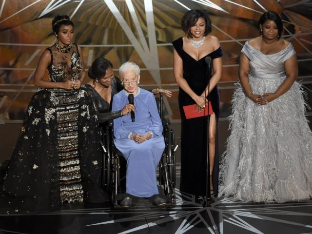 """In this Feb. 26, 2017, photo Janelle Monae, left, Taraji P. Henson, second right and Octavia Spencer, right, introduce Katherine Johnson, seated, the inspiration for """"Hidden Figures,""""(Photo by Chris Pizzello/Invision/AP, File)"""