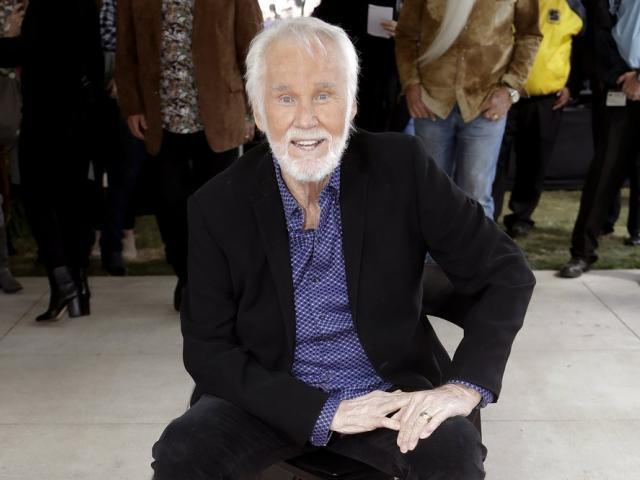 In this Oct. 24, 2017 file photo, Kenny Rogers poses with his star on the Music City Walk of Fame in Nashville, Tenn. (AP Photo/Mark Humphrey, File)
