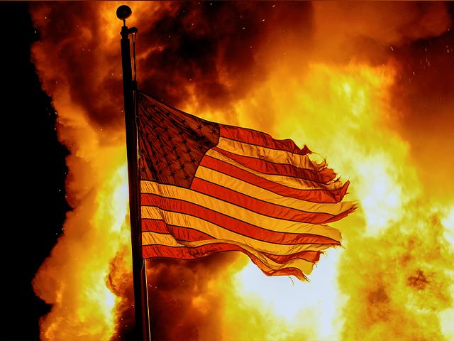 A flag flies over a department of corrections building ablaze during protests on Aug. 24, 2020, in Kenosha, Wis. (AP Photo/Morry Gash)