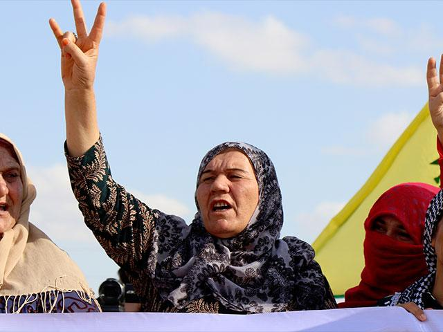 Kurdish women flash victory signs and shout to protest against the expected Turkish military invasion on their areas, at the Syrian-Turkish border, in Ras al-Ayn, Syria, Oct. 7, 2019. (AP Photo)