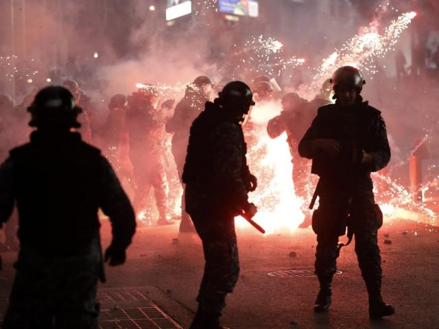 Lebanese riot policemen react to firecrackers that were fired by the supporters of the Shiite Hezbollah and Amal Movement groups in downtown Beirut, Lebanon, Saturday, Dec. 14, 2019. (AP Photo)