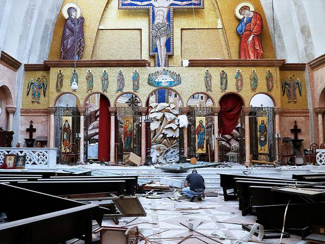 A man removes religious icons from the floor of a damaged church a day after an explosion hit the seaport of Beirut, Lebanon, Wednesday, Aug. 5, 2020.