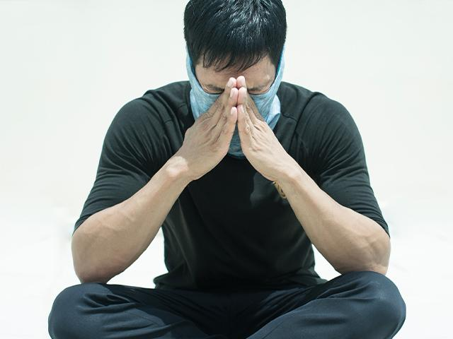 Man praying in surgical mask