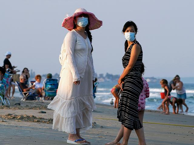 Women wear masks to help prevent the spread of coronavirus at the end of a beach day, Tuesday, Aug. 11, 2020, in Ogunquit, Maine. (AP Photo/Robert F. Bukaty)