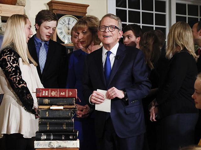 Ohio's 70th Governor Mike DeWine prepares to take oath of office on a stack of nine Bibles. (AP Photo/John Minchillo, Pool)