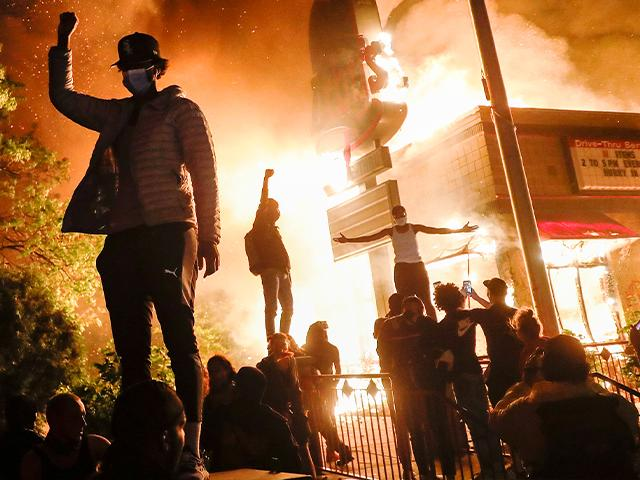 Protestors riot outside of a burning fast food restaurant, May 29, 2020, in Minneapolis. Protests over the death of George Floyd, a black man who died in police custody Monday, broke out in Minneapolis for a third straight night. (AP Photo/John Minchillo)