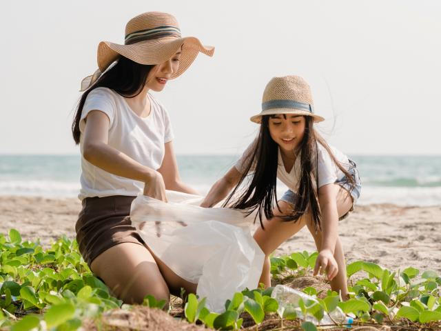 Asian mom and daughter picking up litter from a beach