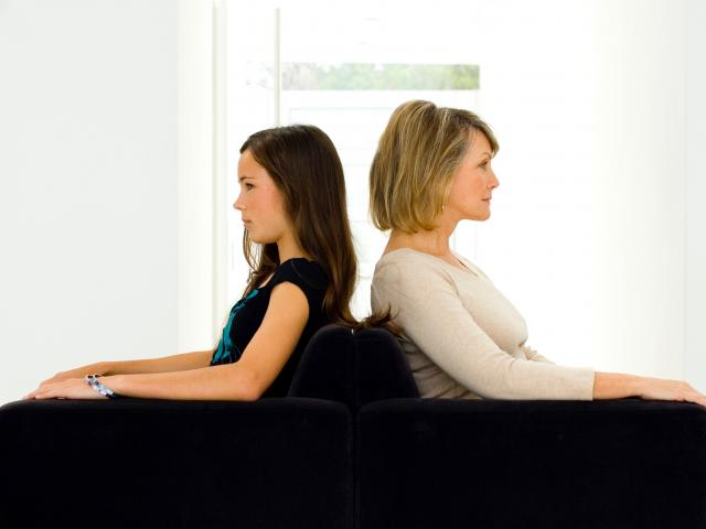 Mom and teen arguing sitting back to back