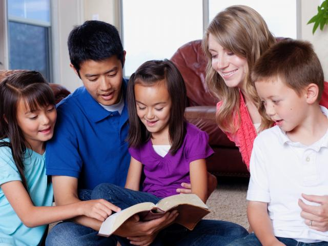 Multicultural family reading the Bible