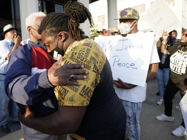 People embrace outside the municipal building in Elizabeth City, NC (AP Photo/Gerry Broome)