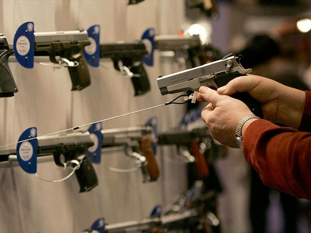 A participant at an NRA Convention holds one of the handguns at a manufacturer's booth. (Image credit: National Rifle Association)