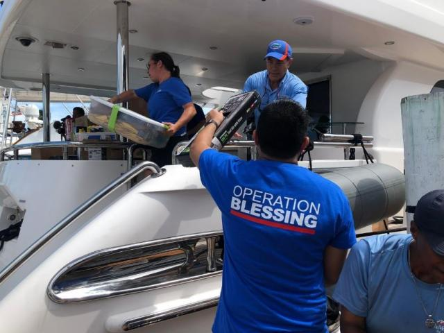 OB teams load a boat with supplies in the Bahamas.