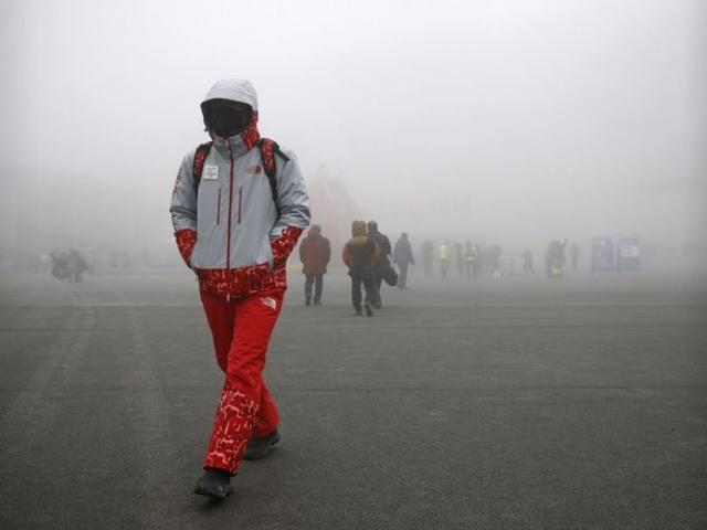 A volunteer walks  in a foggy Pyeongchang Olympic Plaza during the 2018 Winter Olympics in Pyeongchang, South Korea. AP Photo.