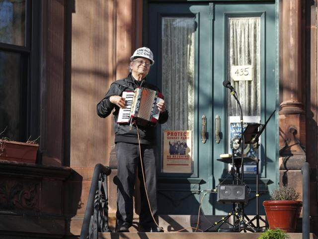 "Paul Stein entertains neighbors with an ""Emergency Accordion Stoop Extravaganza"" (EASE) concert from his stoop (AP Photo/Kathy Willens)"