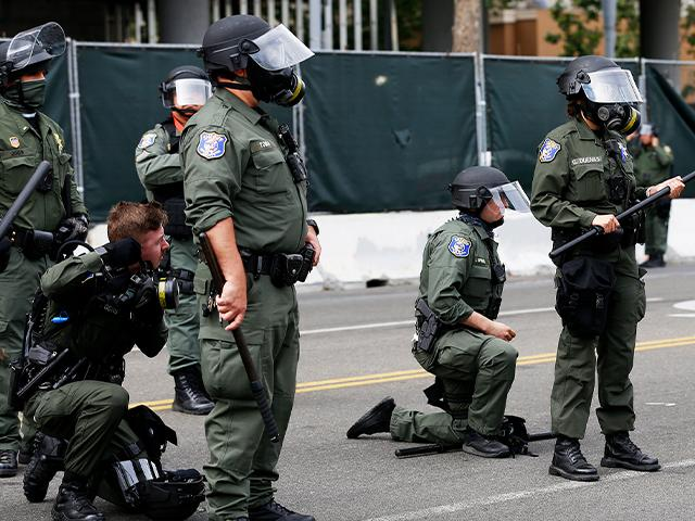 Santa Clara Sheriff's officers take a knee during peaceful protest in San Jose, Calif., Sunday, May 31, 2020 (AP Photo/Josie Lepe)