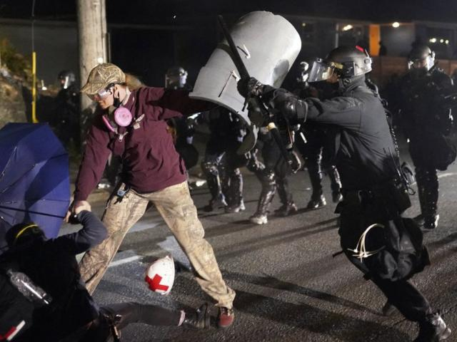 A Portland police officer shoves a protester as police try to disperse the crowd. (AP Photo/Nathan Howard)