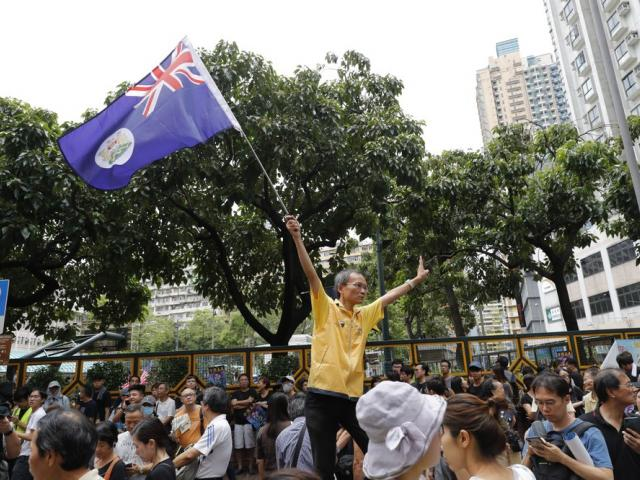 A man waves a colonial British-era Hong Kong flag as people gather at a public park ahead of a planned demonstration in Hong Kong, Saturday, Aug. 3, 2019.(AP Photo/Vincent Thian)