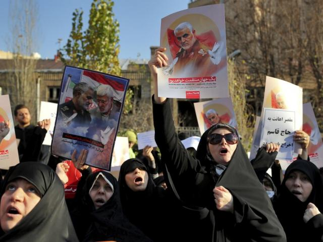 Protesters chant slogans while holding up posters of Gen. Qassem Soleimani during a demonstration in front of the British Embassy in Tehran, Iran, Sunday, Jan. 12, 2020. (AP Photo/Ebrahim Noroozi)