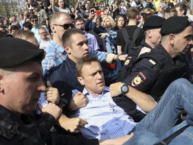 Russian police carry struggling opposition leader Alexi Navalny, center, at a demonstration against President Vladimir Putin in Pushkin Square in Moscow, Russia.