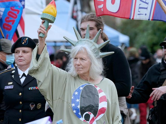A person dressed as Lady Liberty wears a shirt with the letter Q, referring to QAnon, as protesters take part in a protest, Wednesday, Jan. 6, 2021, at the Capitol in Olympia, Wash.,