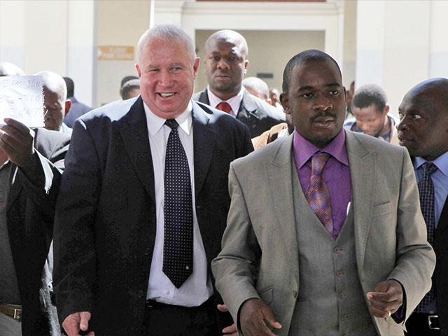 In this May, 10, 2010, AP file photo, Roy Bennett, center left, leaves the High Court in Harare, Zimbabwe, after he was acquitted of terrorism charges.