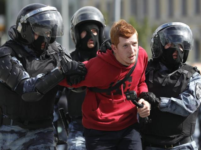 Police officers detain a protestor during an unsanctioned rally in the center of Moscow, Russia, Saturday, Aug. 3, 2019  (AP Photo/ Pavel Golovkin)