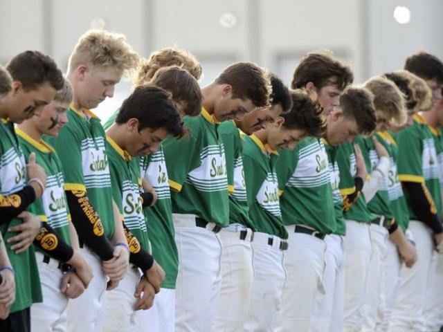 Santa Fe High School baseball players bow their heads in a moment of silence  for the shooting victims at their school before a baseball game against Kingwood Park High School in Deer Park, Texas, Saturday, May 19, 2018.