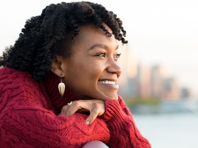 Single woman enjoying life with city skyline in background
